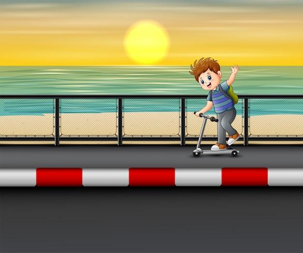 Niño montando un scooter en la carretera cerca del mar