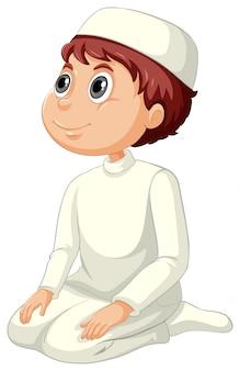 Niño musulmán árabe en vestimentas tradicionales en posición de oración aislado sobre fondo blanco.
