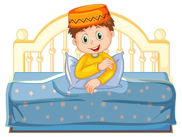 Niño musulmán árabe en vestimentas tradicionales sentado en una cama aislado sobre fondo blanco.