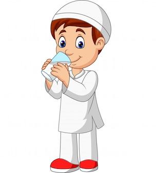 Niño musulmán de dibujos animados bebiendo agua
