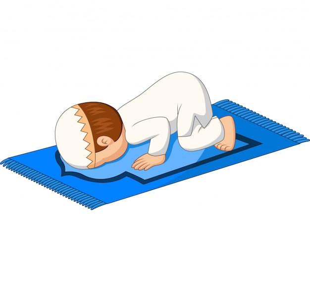 Niño musulmán de dibujos animados oración se inclina hacia abajo en la alfombra
