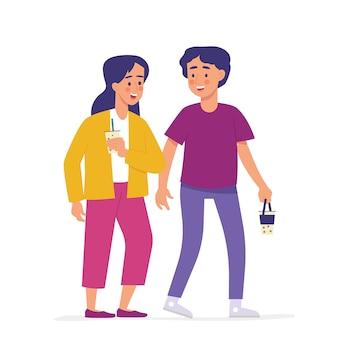 Niño y niña caminan casualmente llevando leche de boba
