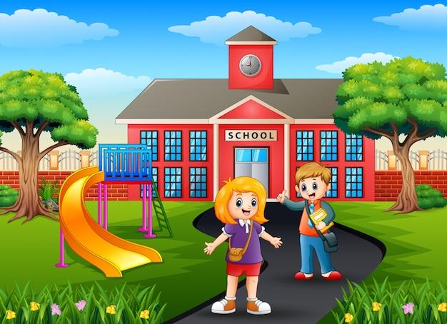 Niño y niña de la escuela con mochilas en frente del edificio de la escuela