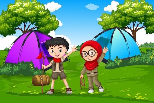 Niño y niña exploradora acampando en el bosque
