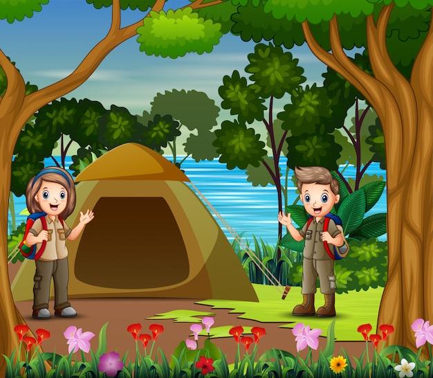 El niño y niña exploradores acampando junto al río
