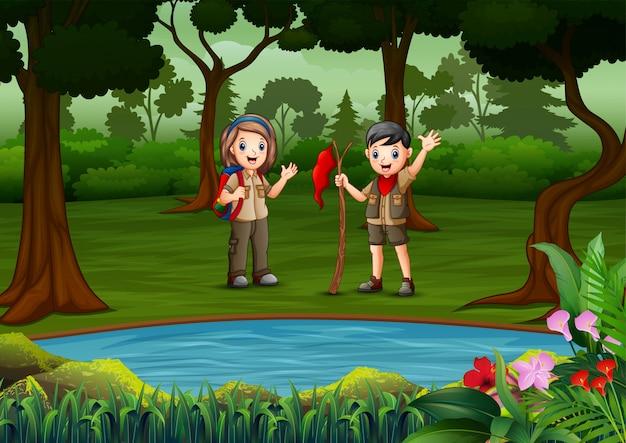 El niño y la niña exploradores descansan junto al lago