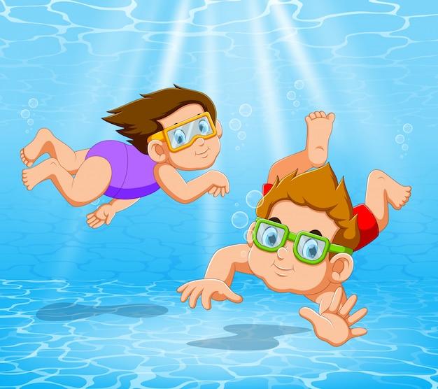 Niño y niña jugando y nadando en la piscina bajo el agua