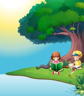 Un niño y una niña leyendo bajo el árbol.