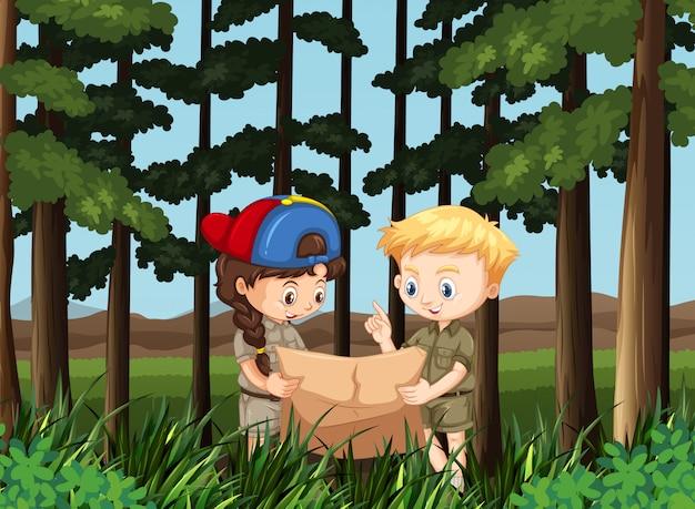 Niño y niña leyendo el mapa en el bosque