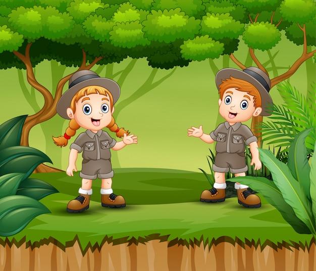 Niño y niña scout de dibujos animados en un bosque