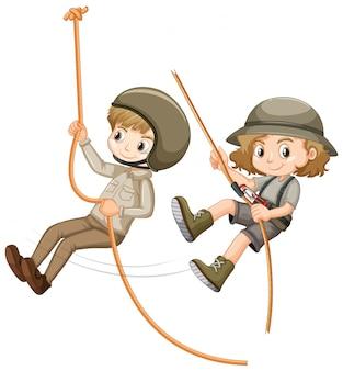 Niño y niña en uniforme scout cuerda de escalada