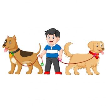 Un niño está parado entre dos perros grandes y lindos y usa una camisa azul