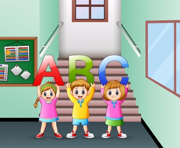 Niño pequeño con carta abc en el pasillo de la escuela