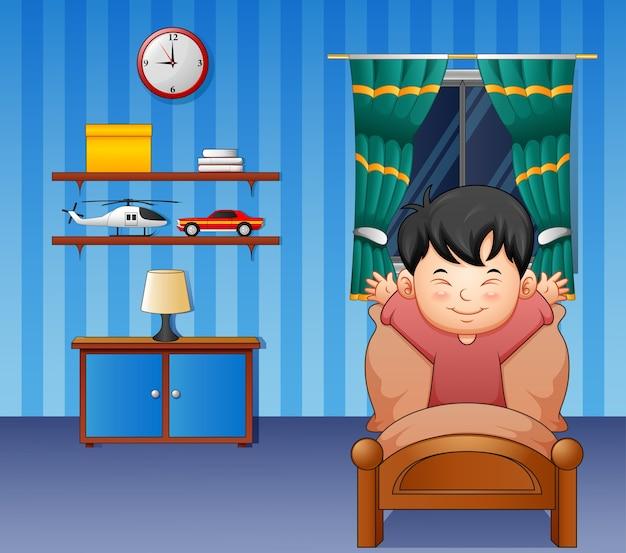 Niño pequeño de dibujos animados despertando en una cama