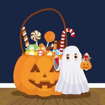 Niño pequeño con disfraz de fantasma y caramelos de calabaza