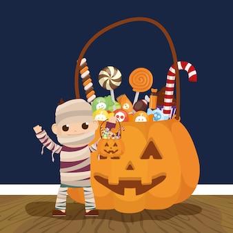 Niño pequeño con disfraz de momia y caramelos de calabaza