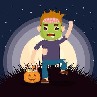 Niño pequeño con disfraz de zombie y caramelos de calabaza