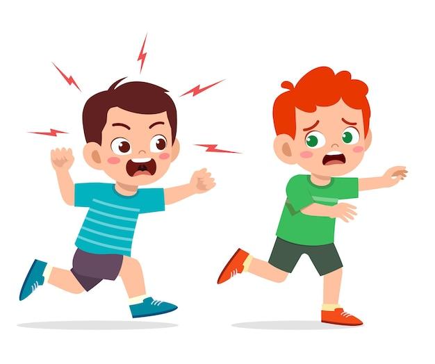 El niño pequeño lindo se enoja y persigue a un amigo asustado