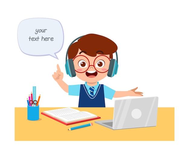 El niño pequeño lindo feliz hace la escuela en casa con la computadora portátil que se conecta al curso y el aprendizaje electrónico del estudio de internet.