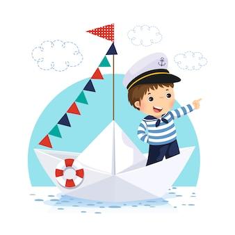Niño pequeño en traje de marinero de pie en un bote de papel