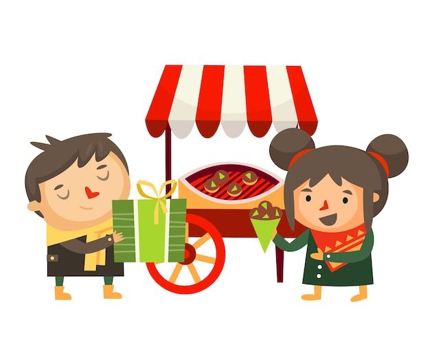 Niño de personajes navideños con un regalo y niña friendo castañas