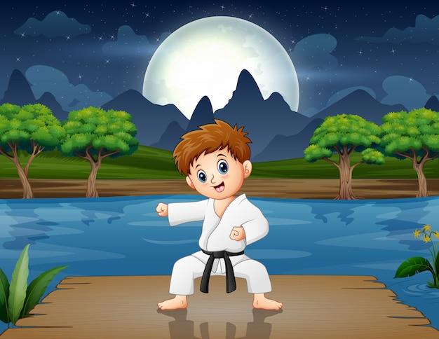 Un niño practicando karate en el muelle por la noche