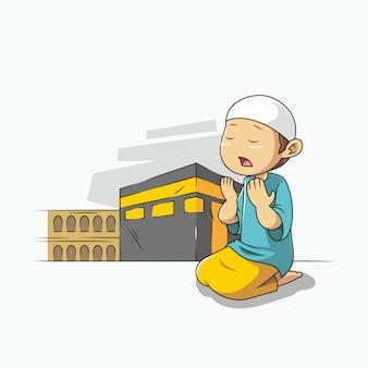Niño reza delante de la meca kaaba.