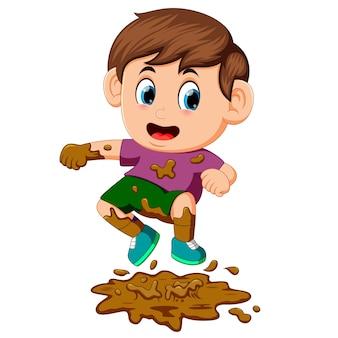 Niño saltando en el barro