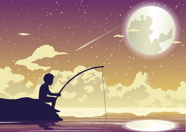 El niño está sentado a pescar en una hermosa noche
