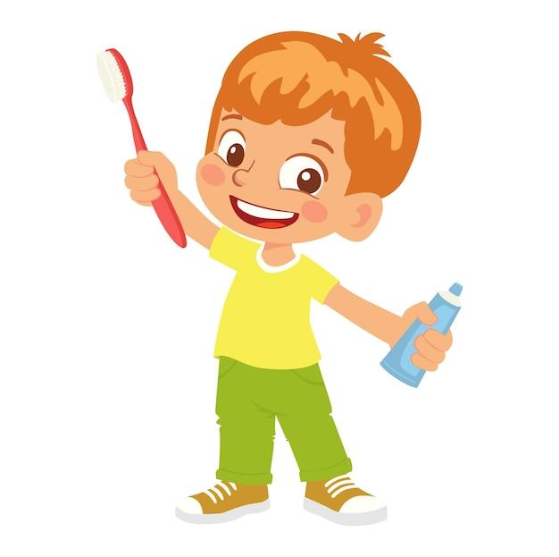 Niño sosteniendo un cepillo de dientes y pasta de dientes