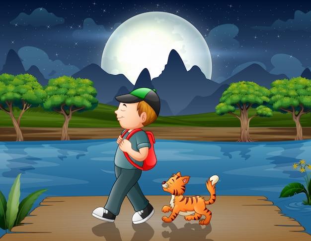 Niño con su gato caminando en el muelle