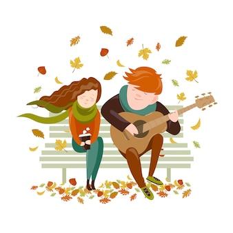 Niño toca la guitarra para una niña en el parque otoño