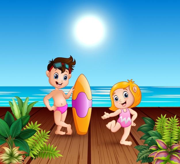 Niño en traje de baño sosteniendo una tabla de surf con una chica en el muelle