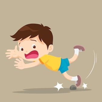 El niño tropezaba con una roca mientras caminaba.