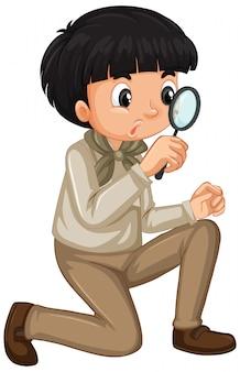 Niño en uniforme de explorador con lupa aislado
