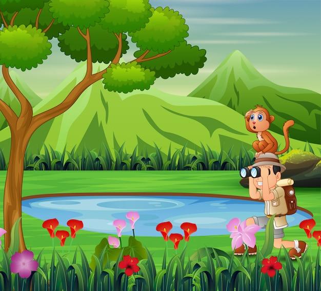 Niño usando binoculares con un mono cerca del pequeño estanque