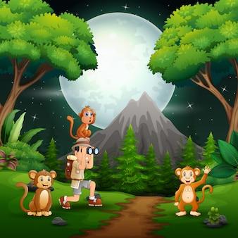 Niño usando binoculares con monos en un bosque