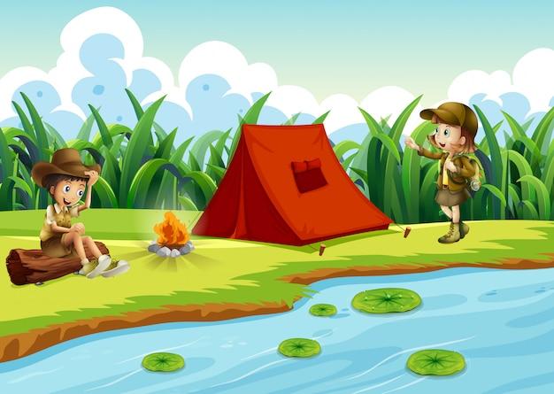 Niños acampando junto al agua con una carpa.