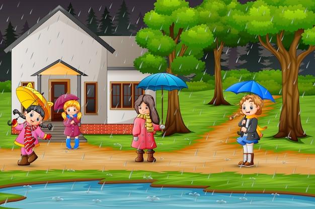 Niños caminando bajo el cielo lloviendo con una sombrilla.