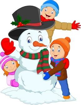 Niños de dibujos animados jugando con muñeco de nieve