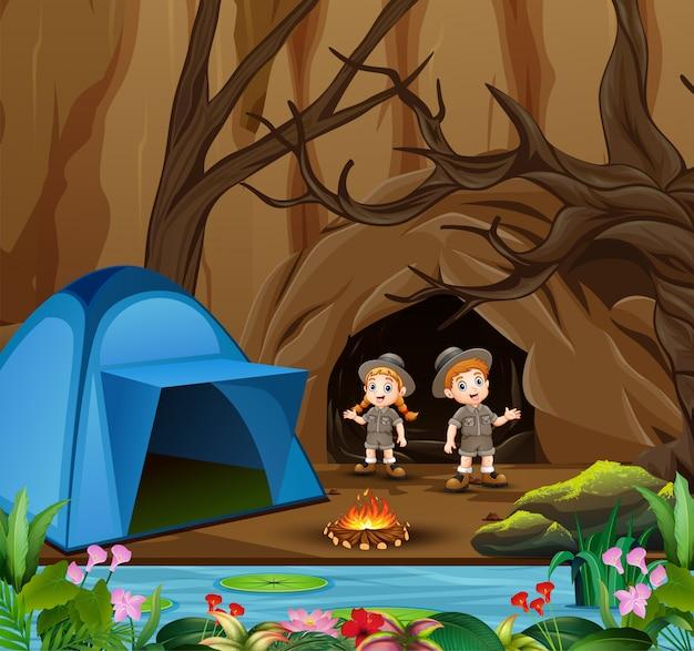 Niños de dibujos animados en traje de explorador acampando cerca de la cueva