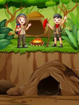 Niños de dibujos animados en traje de explorador acampando en la naturaleza
