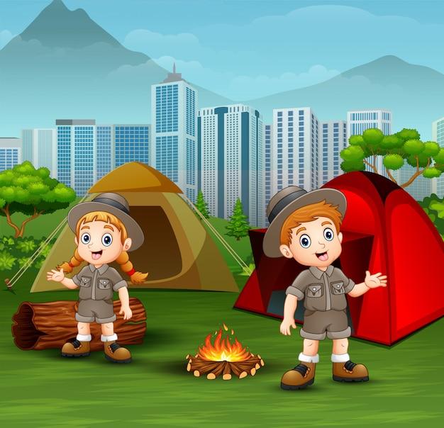 Niños de dibujos animados en traje de explorador acampando en el parque de la ciudad