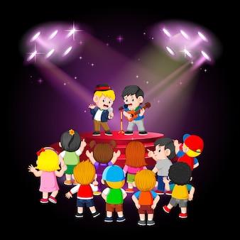 Los niños disfrutan de la actuación de los amigos.