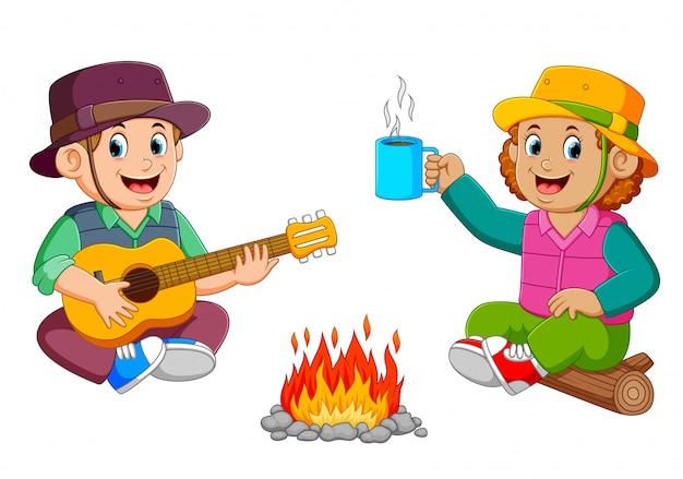 Los niños disfrutan del campamento tocando la guitarra con una taza de café.