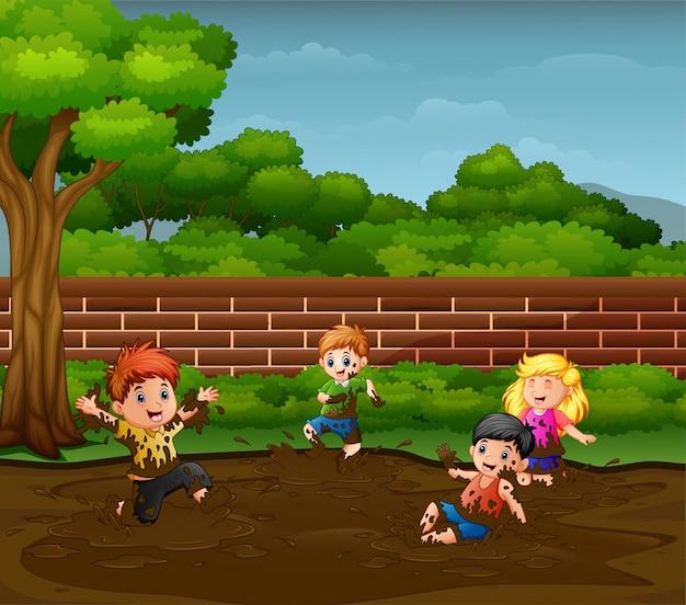 Niños divirtiéndose jugando en el barro