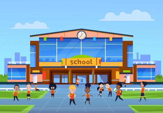 Niños en el edificio de la escuela. niños de dibujos animados en uniforme juegan en el patio frente a la universidad. regreso a la escuela, educación