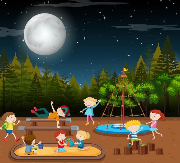 Niños en la escena nocturna del parque.