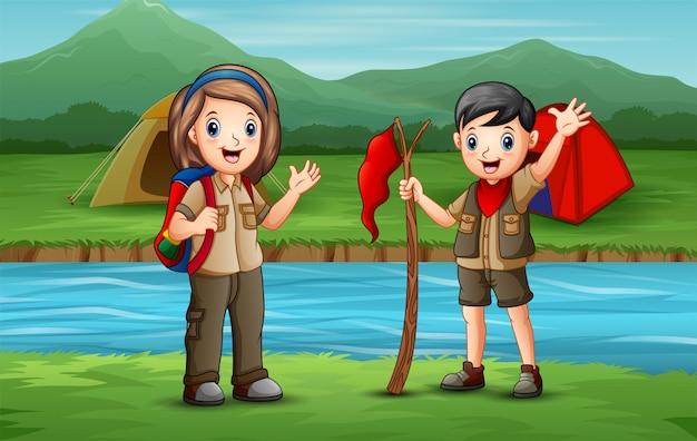 Niños exploradores felices acampando junto al río