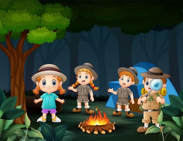 Niños felices acampando en el bosque por la noche cerca del gran fuego